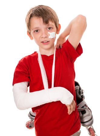 portrait of boy with a broken arm holding roller skates, isolated over white photo