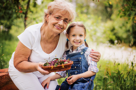 cute little girl with her grandmother holding cherries  in the garden