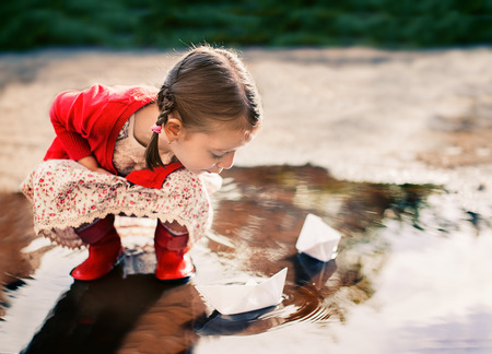 tar paper: cute little girl playing with paper boat