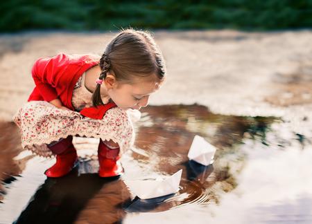 botas de lluvia: linda niña jugando con barco de papel