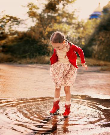 botas de lluvia: niña linda que llevaba botas de lluvia rojas saltando en un charco