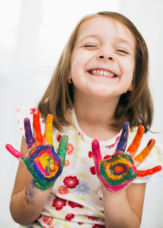 messy kids: Portrait of a cute cheerful happy little girl showing her hands painted in bright color