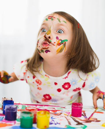 cute little girl is painting with gouache photo