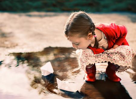 Linda niña jugando con barco de papel Foto de archivo - 30976355