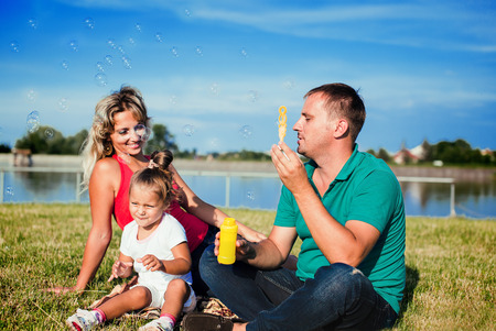 happy family blowing soap bubbles  outdoors photo
