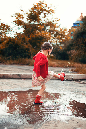 puddle: cute little girl wearing red rain boots jumping into a puddle