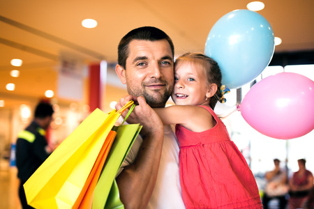 happy father with cute little daughter shopping in mall photo