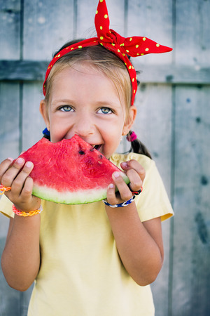 closeup summer portrait of a  cute happy little girl  with big red slice of watermelon