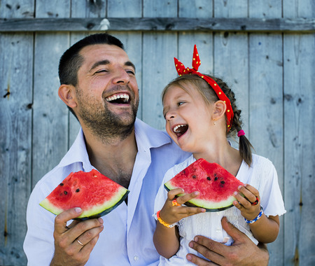 happy father playing with cute little daughter holding  watermelon photo