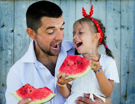 スイカを持ってかわいい小さな娘と遊んで幸せな父