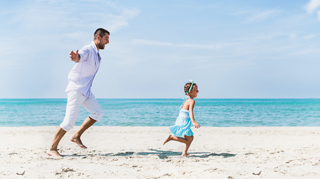 Healthy father and daughter playing together at the beach photo