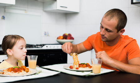 father with daughter eating pasta with sauce for the dinner photo