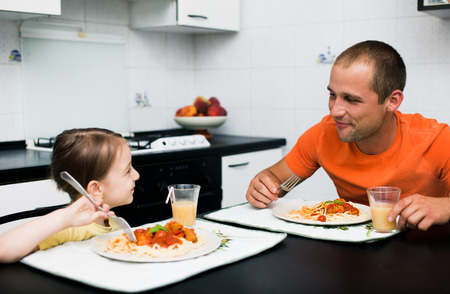 father with daughter eating pasta with sauce for the dinner Фото со стока
