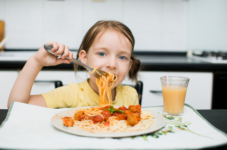 cute little girl eating spaghetti with tomato sauce and vegetables for dinner