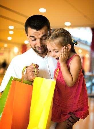 padre e hija: feliz padre con la peque�a hija linda de compras en el centro comercial Foto de archivo