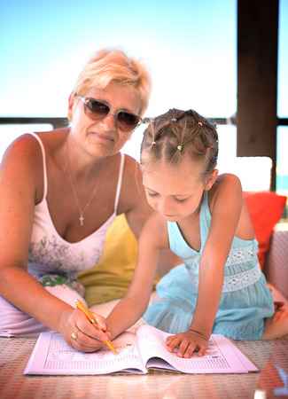 Grandmother teaches her granddaughter to write letters  photo
