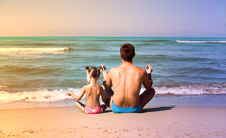 joga: father with daughter in a lotus position doing joga exercises
