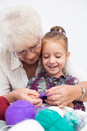 cute little girl and her granddaughter knitting together photo
