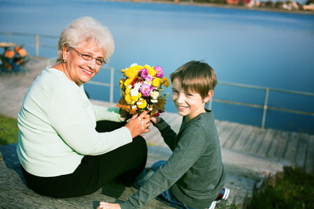 grannies: happy grandson giving flovers to grandmother outdoors