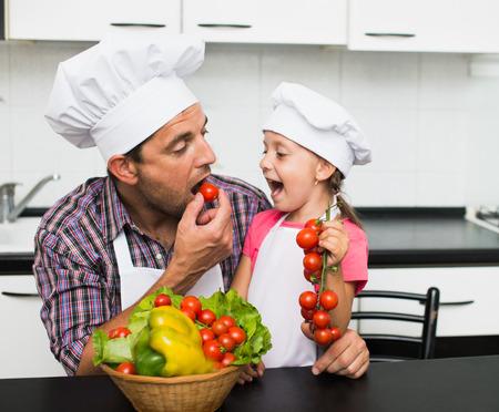 niños cocinando: padre feliz con su pequeña hija preparar una ensalada en su cocina