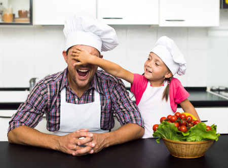 father's: happy father with his little daughter preparing a salad in their kitchen Stock Photo