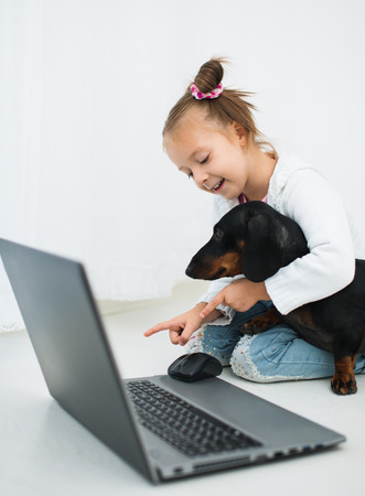 Cute Little Girl  And Dachshund Use Laptop photo