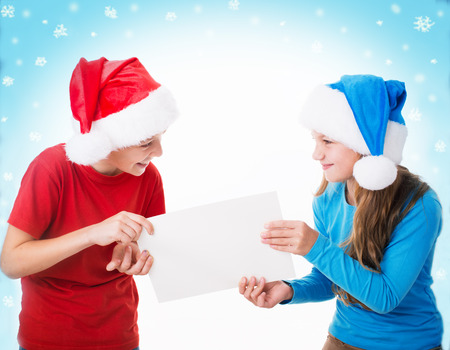 two children in santa hats are holding blank board , isolated over white photo
