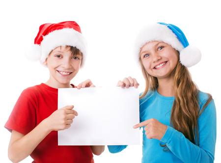 two children in santa hats are holding blank board and pointing to it , isolated over white photo