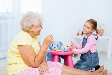 little girl plays with grandmother with her toys photo