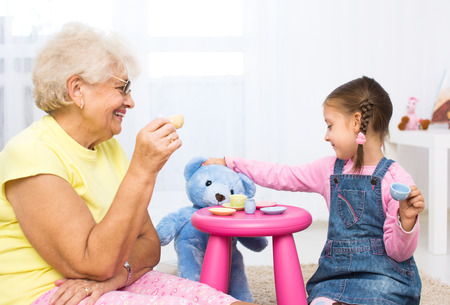 little girl plays with grandmother with her toys