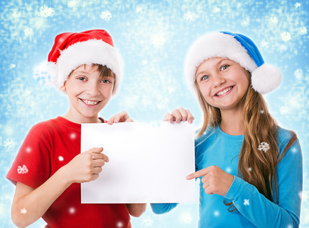 two children in santa hats are holding blank board and pointing to it photo