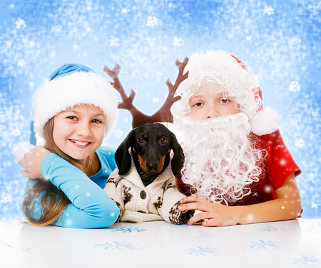 children plays with dachshund in Christmas masks of Santa, Snow Maiden and deer Фото со стока