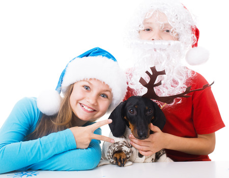 plays: children plays with dachshund in Christmas masks of Santa, Snow Maiden and deer, isolated over white