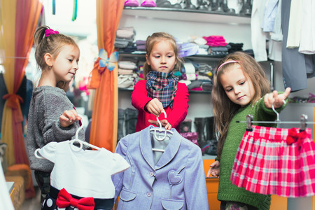 clothing store: three smiling little girls shopping in retail store