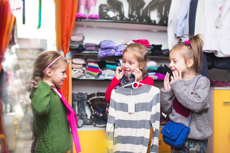 clothing stores: three smiling little girls shopping in retail store