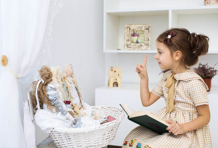 baby doll: Portrait of a little girl reading book to her textile handmade princess dolls