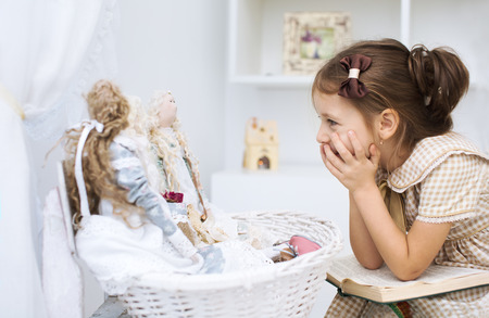 toy story: Portrait of a little girl reading book to her textile handmade princess dolls