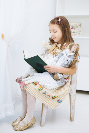 Portrait of a little girl reading book to her textile handmade princess dolls