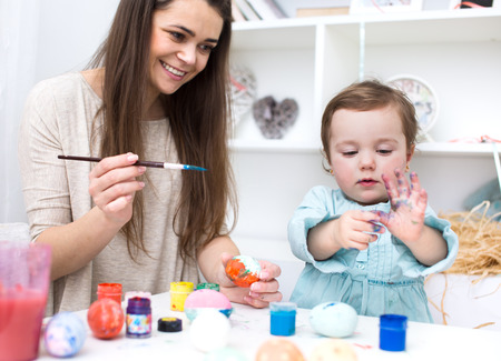 multi coloured: Loving mother and her baby painting easter eggs