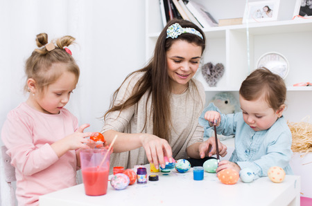 Loving mother and her little daughters painting easter eggs photo