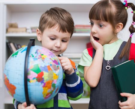 happy planet earth: Los ni�os peque�os est�n examinando globo en el aula