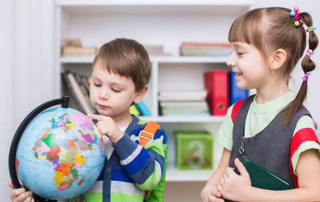 Little kids are examining globe in the classroom Standard-Bild