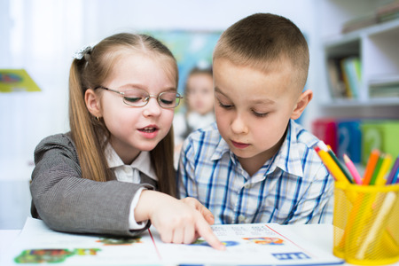 Little schoolchildren are reading book at school photo