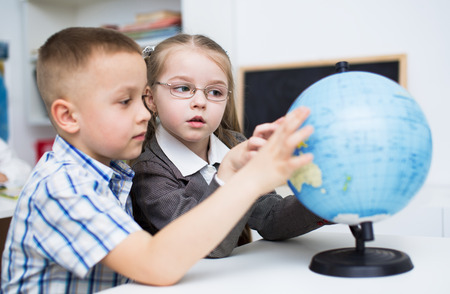 schoolkid search: peque�os schoochildren est�n examinando mundo Foto de archivo