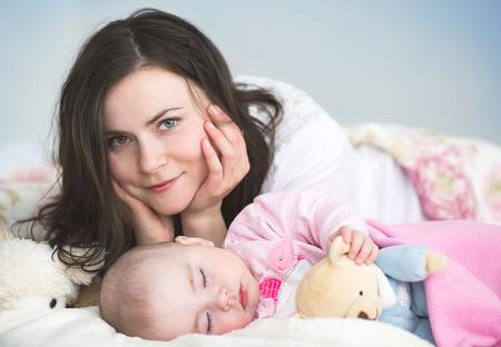 Jonge moeder met haar slapende baby in bed
