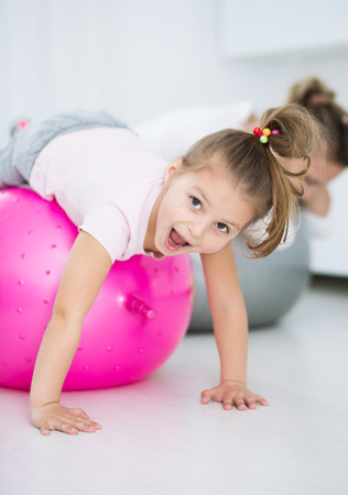 Mother with daughter doing gymnastic exercises with balls Stock Photo