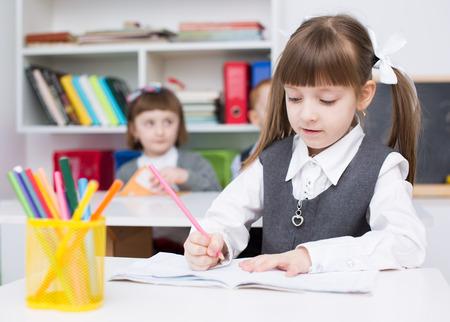Portrait of cute little girl drawing in copybook