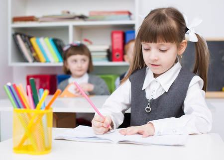 Portrait of cute little girl drawing in copybook Фото со стока - 39363831