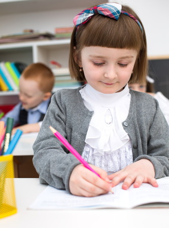 copybook: Portrait of cute little girl drawing in copybook