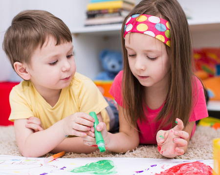 art activity: two little kids painting with paintbrush and colorful paints